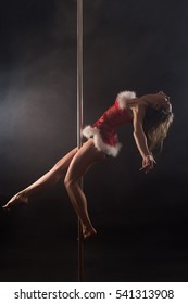 Girl, dressed santa outfit, makes pole dance exercise