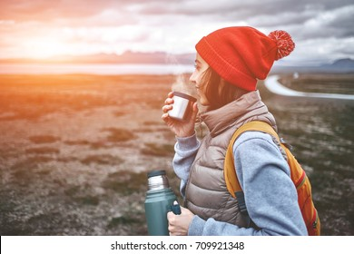 Girl dressed in a sweatshirt, a vest and a red knitted hat hold a iron cup and drink a hot tea on background of mountains and lake. Valley and national park Thingvellir, Iceland