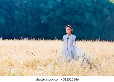 Girl dressed in traditional ethnic costume stands on a background of forest and field
