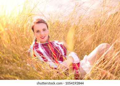 Girl dressed in a traditional Ukrainian attire lying in a field of grass