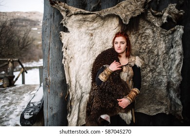 The girl dressed in a Viking outfit. Red hair
