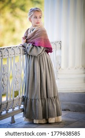 girl dressed in vintage style, an elegant young lady is walking on the terrace of an old mansion. Long dress in the style of the nineteenth century, knitted shawl on the shoulders.