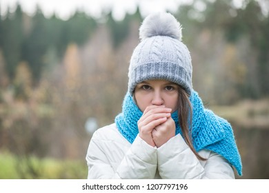 The girl is dressed in warm clothes, warm hands. Autumn, cold outside
