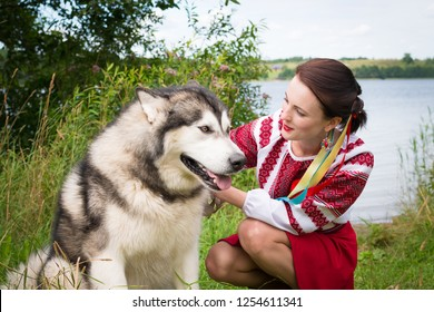 Girl dresses in a traditional Slavic attire petting a dog