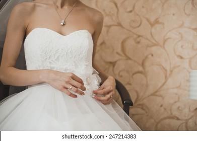 The girl dresses a wedding dress.