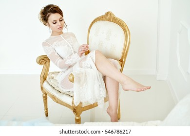 girl in a dressing gown sits in a gilded chair
