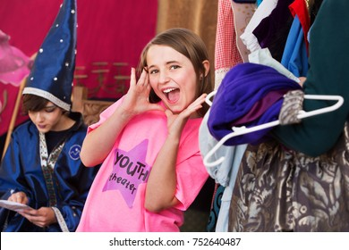 Girl in dressing room wearing pink shirt places hands by mouth and shouts with glee