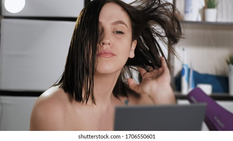 Girl dries hair with hairdryer. Young woman holds hairdryer in her hands and directs it to her head, her hair develops beautifully in wind. Makeup at home, hair care, hairstyle self concept. Close-up