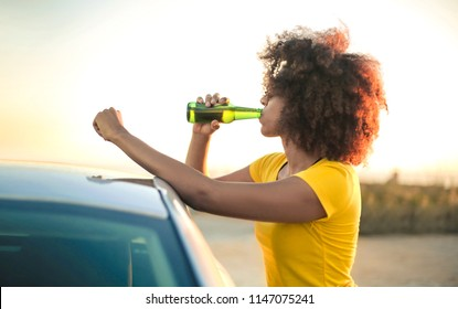 Girl drinking a beer while relaxing after traveling by car