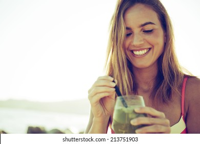 girl drinking a cocktail at sunset