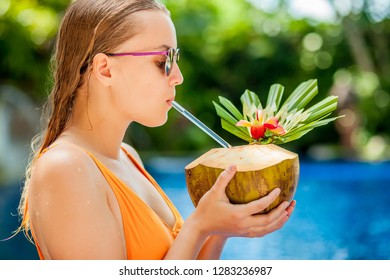 Girl drinking a coconut in the pool