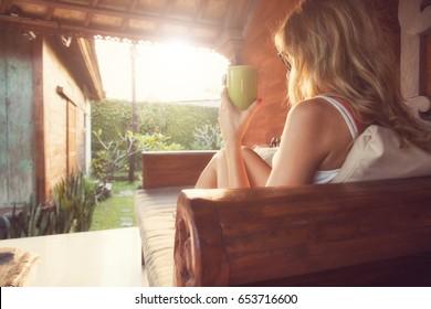 Girl drinking coffee / tea and enjoying the sunrise / sunset in garden.