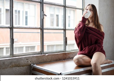 Girl drinking Coffee or Tea look at the camera with a relaxing expression near window wearing a long sleve sweater of wine color