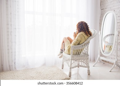 girl drinking coffee or tea in morning sunlight near window. girl in a knitted jacket looking through a window, sitting back, drinking tea and sad, white interior of the house