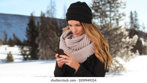 Girl drinking coffee or tea outside in the snow and laughing at a message