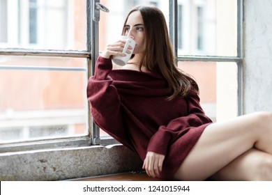 Girl drinking Coffee or Tea while daydreaming near window wearing a long sleve sweater of wine color