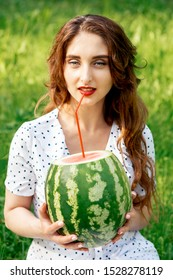 Girl is drinking fresh watermelon juice from cocktail straw while holding whole watermelon and looking at camera. Sip of freshness.