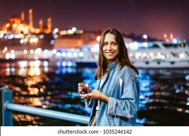 Girl drinking hot tea by the bosphorus. Istanbul Turkey