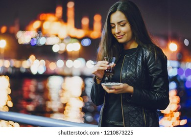 girl drinking hot tea by the bosphorus in Istanbul Turkey