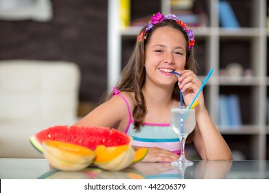 Girl drinking lemonade in front of her was watermelon and melon