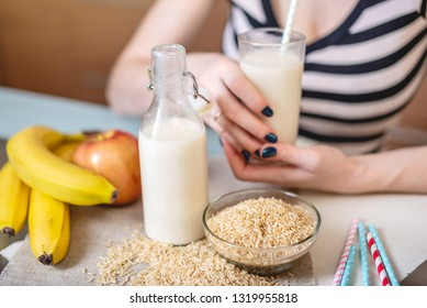 Girl drinking organic rice milk holding a glass Cup in her hands in the kitchen. Bottle and fruit on the table. The view from the top. Diet healthy vegetarian product