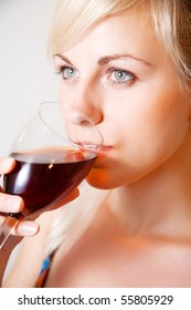 Girl drinking red wine from goblet