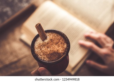 Girl drinking salep (milky traditional hot drink) while reading book