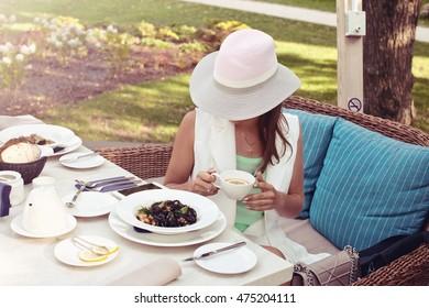 Girl Drinking Tea and eating black pasta with shrimp in restaurant, summer terrace.