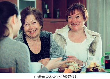 Girl drinking tea with positive female pensioners and laughing