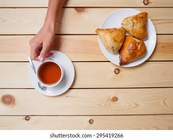 Girl drinking tea with uzbek national dish somsa