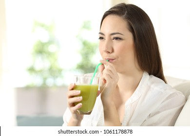 Girl drinking vegetable juice from a glass sipping a straw sitting on a couch in the living room at home