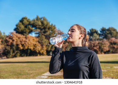 Girl drinking water after training