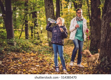 Girl drinking water in the forest behind her is her mother and her small yellow dog