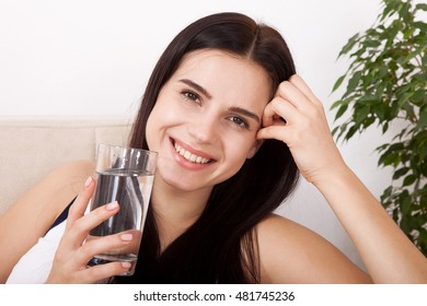 Girl drinking water at home and looking at camera. Glass of water in the morning before breakfast, horizontally