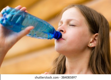 Girl drinking water outdoors with closed eyes - very shallow depth of field