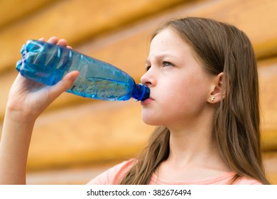 Girl drinking water outdoors - very shallow depth of field