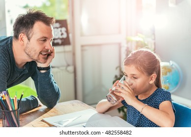 Girl drinking water while doing homework and father standing next to her