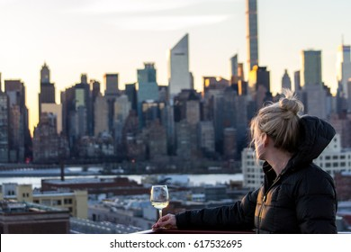 Girl drinking wine in New York City at sunset - rooftop bar