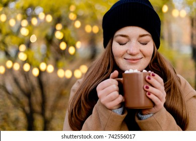Girl drinks cocoa with marshmallow. Cozy winter morning, New Year's and Christmas holidays
