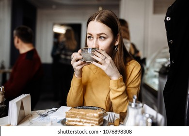 Girl drinks coffee and eat dessert in cafe