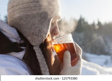 girl drinks tea over winter nature background outdoor