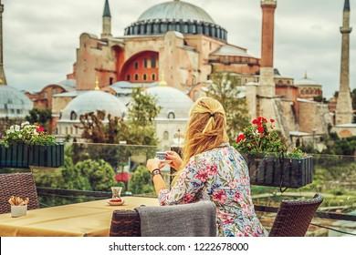 Girl drinks Turkish coffee enjoying the view of the Hagia Sophia Museum. Istanbul, Turkey.