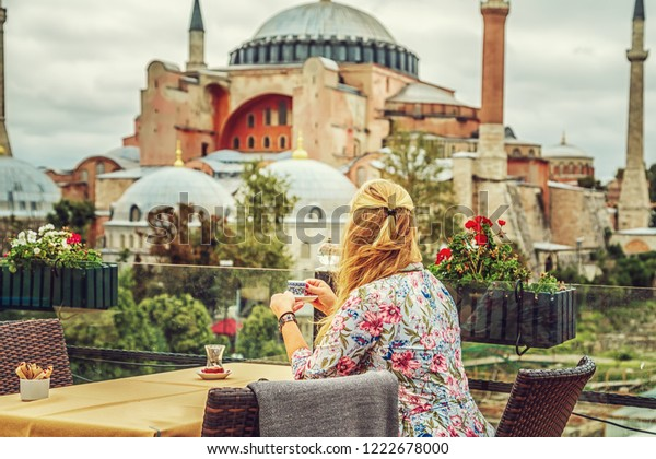 Девушка пьет турецкий кофе, наслаждаясь видом на музей Святой Софии. Стамбул, Турция.