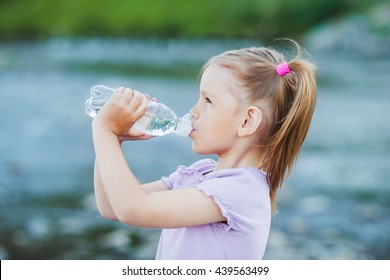Girl drinks water from a bottle, outdoor