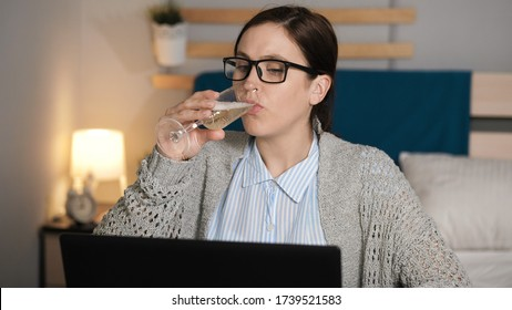 Girl drinks wine and works at computer. Woman with glasses alone in bedroom sits at desk typing on laptop keyboard and drinking champagne. Work at home, freelance concept
