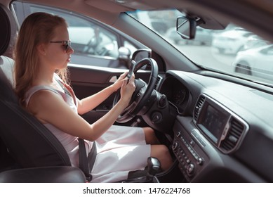 A girl driving a car reads and writes a message on the phone, an online application, parking at the store, waiting on a smartphone, in the summer in the city