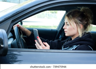 Girl driving car and texting on her smart phone