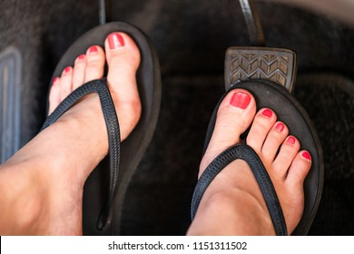 A girl is driving her car wearing flip flops.