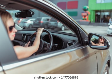 A girl driving a right-hand drive car is parked in a parking lot, near a shopping center, left-hand traffic. Close-up rear view mirror, steering wheel driver with glasses