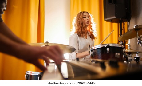 Girl drummer and a guy on keyboards. Focus from hands to drums. Backlight